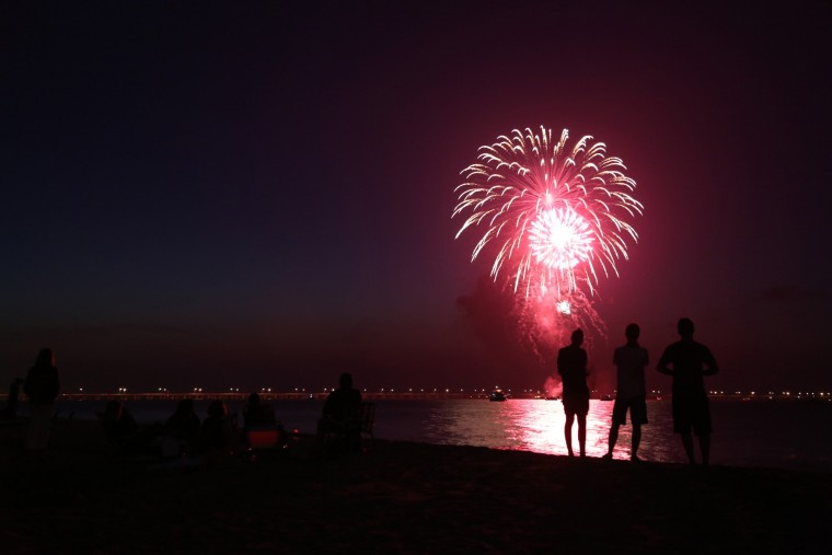 People gather along the beach near the Aeries on the Bay area of Virginia Beach to watch holiday fireworks at dusk on Saturday, July 12, 2014. The fireworks are privately- funded by the three area civic leagues along that part of the bay, including Chic's Beach. (Martin Smith-Rodden | The Virginian-Pilot)