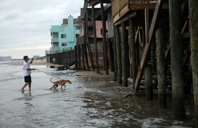 Chic's Beach resident Taylor Sharpe and his dog Sandy walk the beach there at high tide on Aug. 28, 2011, after the departure of Hurricane Irene. Waves from the Chesapeake Bay lap at the pilings of the waterfront homes on Ocean View Avenue in this section of Virginia Beach. (Vicki Cronis-Nohe | The Virginian-Pilot)