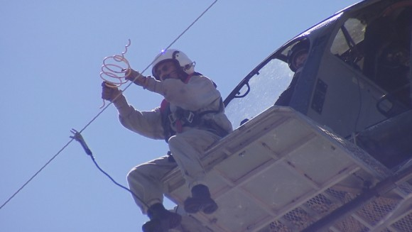 A flight crew from Haverfield Aviation attaches a bird repellent called a firefly to power lines beside the Lesner Bridge in Virginia Beach. Credit: Walter Hildebrand/WAVY TV