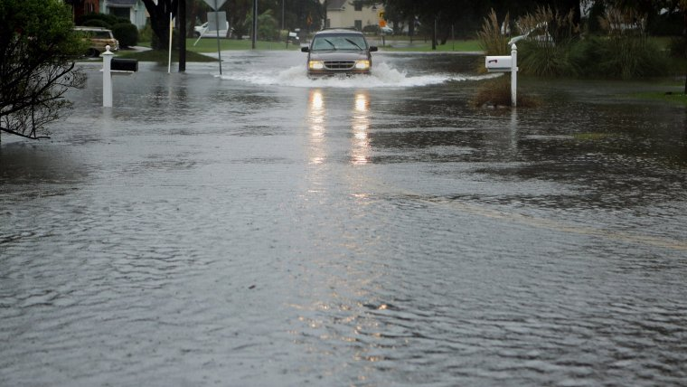 A vehicle makes it way slowly through the rising water on Lynnhaven Drive in Virginia Beach on Friday, Oct. 2, 2015, several hours before high tide. (Vicki Cronis-Nohe | The Virginian-Pilot)