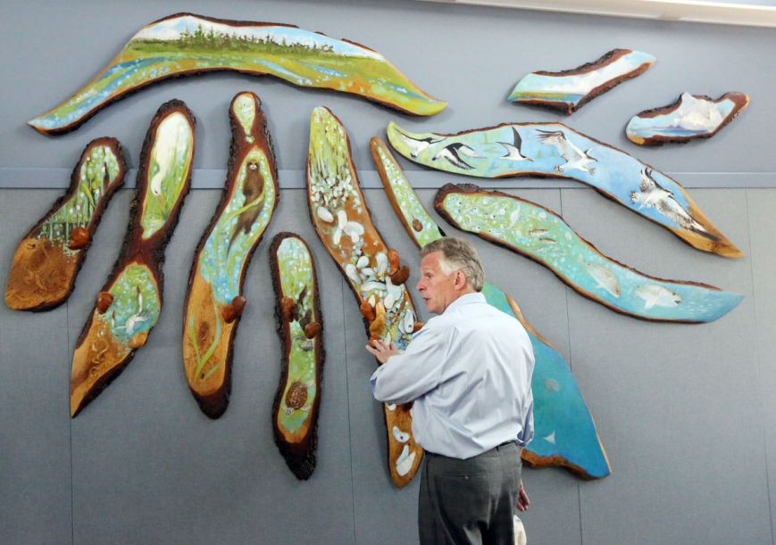 Gov. Terry McAuliffe looks at art made of a live oak tree during a tour . . .   Photo Credit: Steve Early | Virginian-Pilot